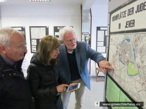 """Volker Landig vom Arbeitskreis Gröschlerhaus zeigt dem Besuch eine Tafel der Ausstellung """"Zur Geschichte der Juden Jevers"""""""
