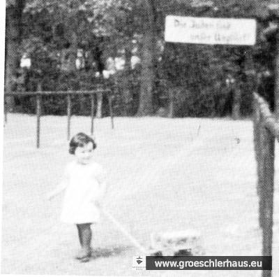 """Die 3jährige """"Halbjüdin"""" Eva Hirche vor dem Schild """"Die Juden sind unser Unglück"""". Das antisemitische Schild befand sich am Alten Markt, direkt vor der Graft."""