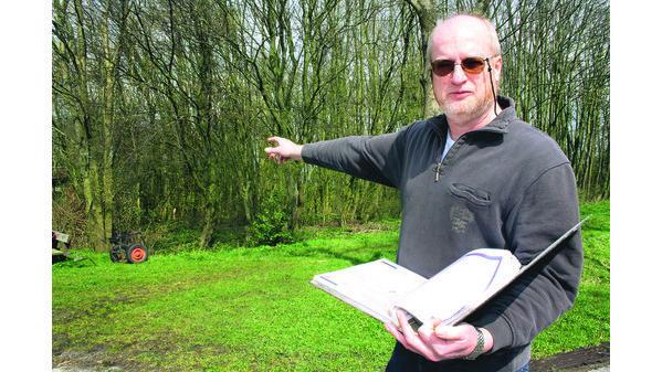 """Der Historiker Holger Frerichs zeigt auf das Wäldchen direkt am Ems-Jade-Kanal, auf dessen Gelände sich das Kriegsgefangenenlager """"Sander Mühle"""" befand. Es ist zu vermuten, dass an den Wurzeln noch Grundmauerreste erhalten sind. (Foto von 2012, NWZ)"""