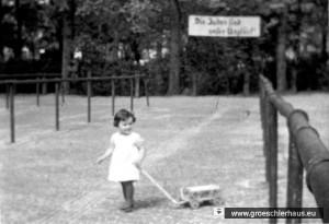 """Die dreijährige Eva Hirche 1936 auf dem Alten Markt von Jever vor dem Plakat """"Die Juden sind unser Unglück"""". Es handelt sich um ein Einzelbild aus einem Schmalfilm, den der Vater in aufklärerischer Absicht drehte. (Foto A. Hirche)"""