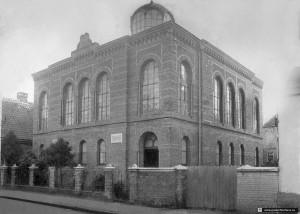 Die Synagoge von Jever, um 1900 (Bildarchiv Pisarek akg-images). Das im Nachlass des bekannten Berliner Fotografen Abraham Pisarek (1901 – 1983) jüngst aufgefundene Foto entstand um das Jahr 1900 herum. Die Datierung ist aufgrund der Höhe der Koniferen und wegen der Elektroleitungen, die es in Jever erst nach 1896 gab, möglich.