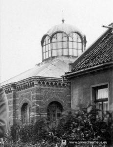 Ein Polizist präsentiert auf einem Balkon gegenüber der Synagoge sich und seine Braut dem Fotografen, der aber aus Versehen auf den Hintergrund scharf gestellt hat. So entstand ca. 1936 das bisher deutlichste, bekannte Foto der Dachpartie. (Ausschnitt, Sammlung P. Gabriels, Jever)