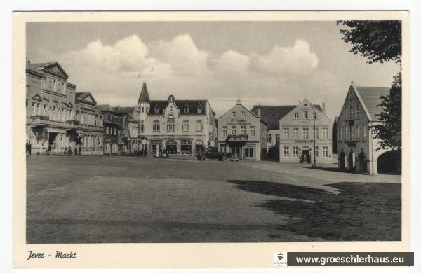 """Abb.: Blick auf den Alten Markt in Jever mit den Hausnummern 2 (Möbelhändler Popken) und Nr. 3 (""""Schwarzer Adler""""), im Hintergrund zwischen beiden Gebäuden ein großes Lagerhaus. Postkarte von 1954. Schlossmuseum Jever. PK 1926."""